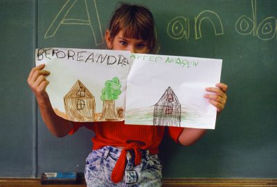 Photo: A young girl holds up before and after drawings of her house after hurricane Andrew destroyed it.
