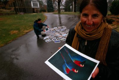 Photo: Rosa Maria Ruiz, a guide from Bolivia, holding a laminated photograph in the rain to make sure they are waterproof.