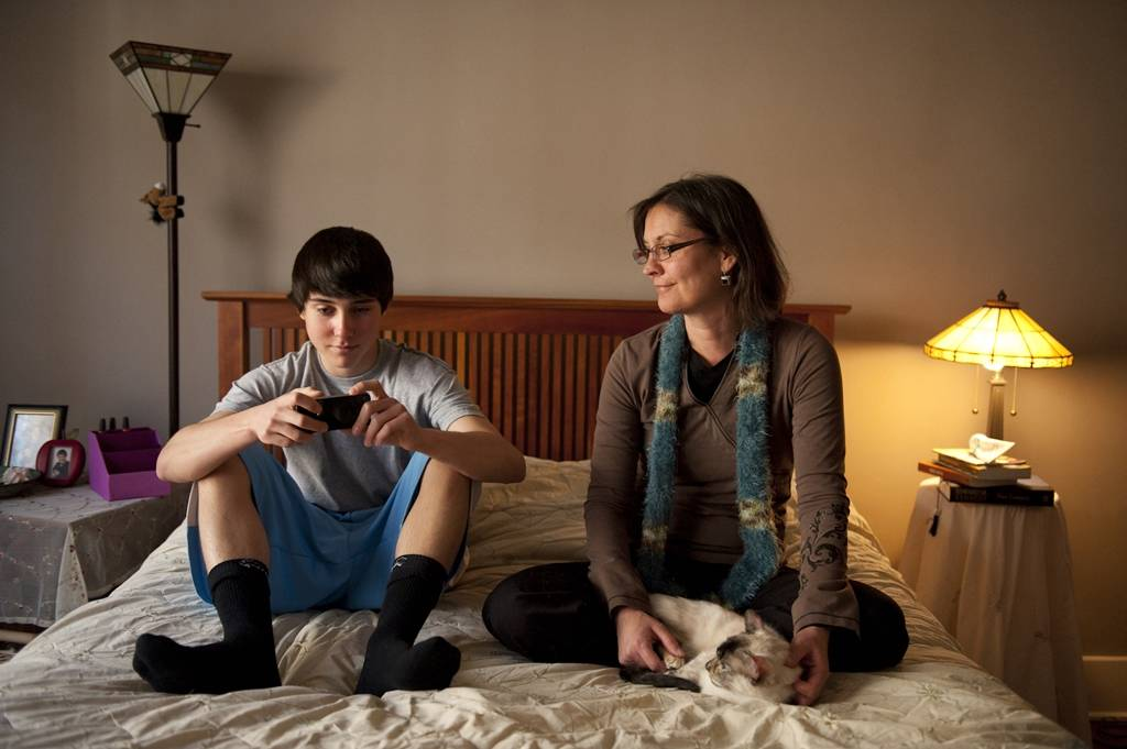 Photo: A teenage boy uses his phone while spending time with his mother.