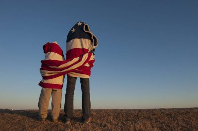 Photo: An American flag draped around two people.