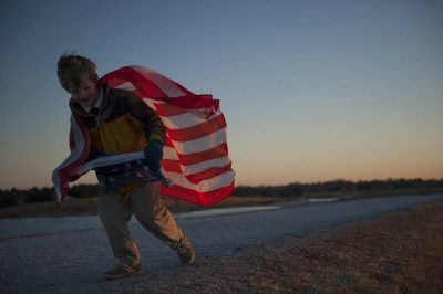 Photo: A young boy runs with an American flag.