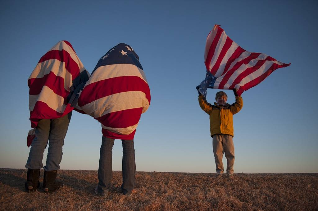 Photo: Three people drape themselves with American flags.
