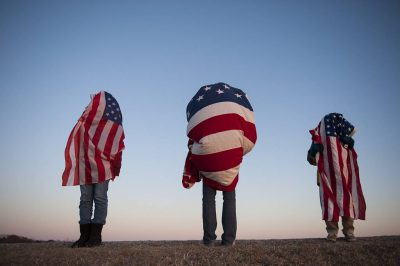 Photo: Three people draped with American flags.