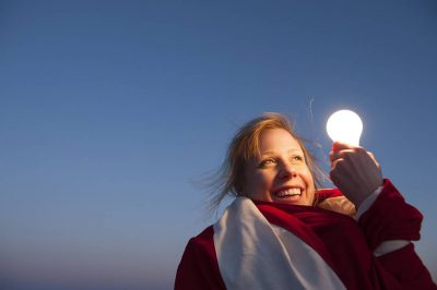 Photo: A young woman holds a light bulb while clothed in an American flag.