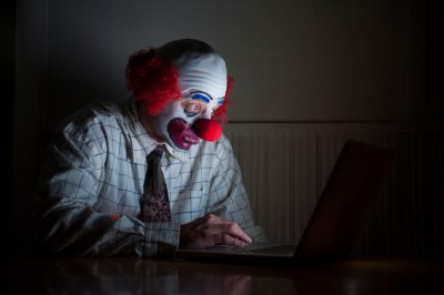 Photo: A clown simultaneously uses his phone and computer.