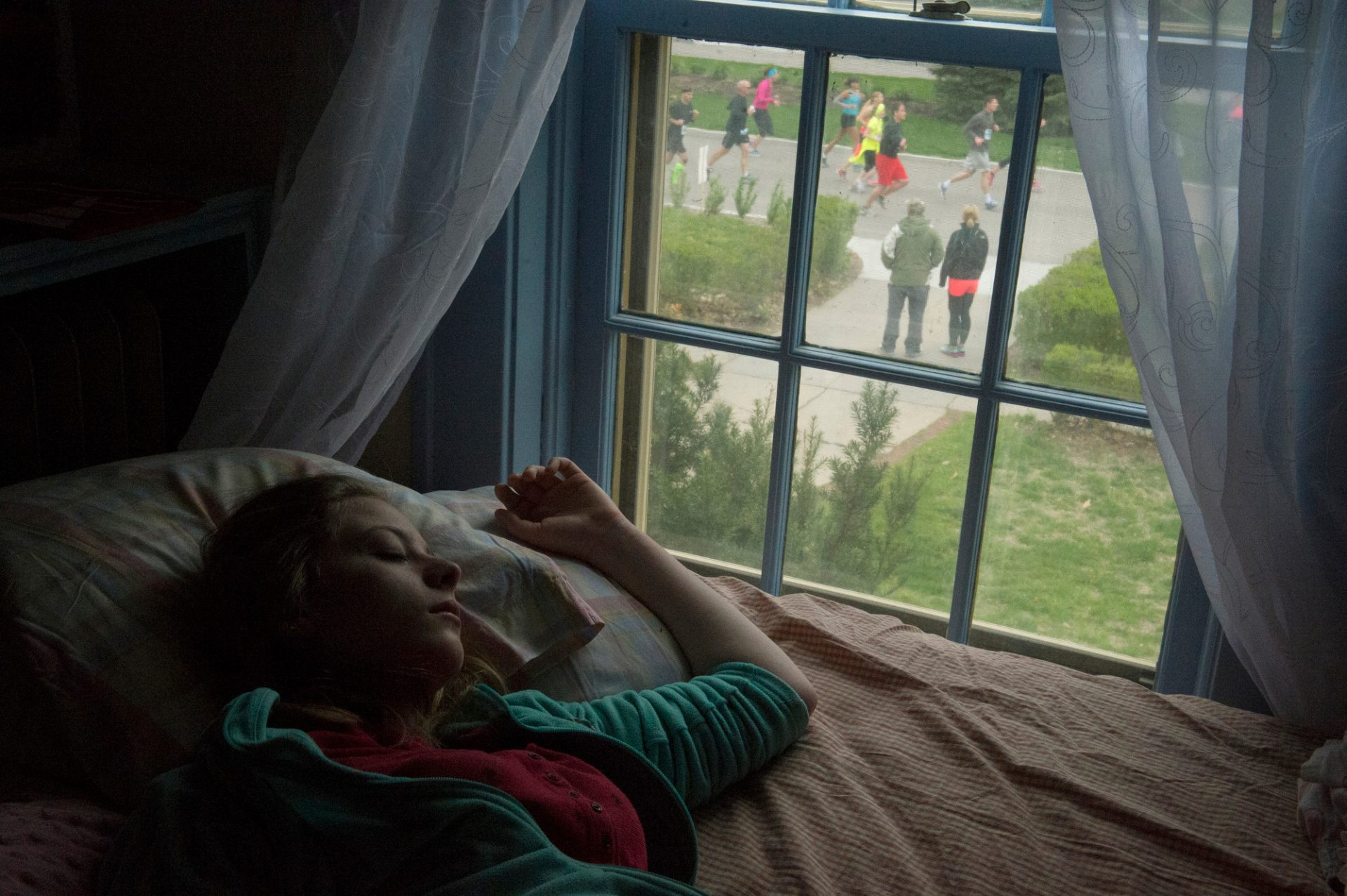 Photo: A teenage girl sleeps while marathoners run by her house in Lincoln, Nebraska.