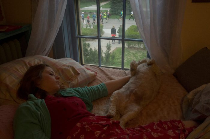 Photo: A teenage girl sleeps with her dog while marathoners run by her house in Lincoln, Nebraska.