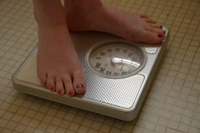 Photo: A woman weighs herself.