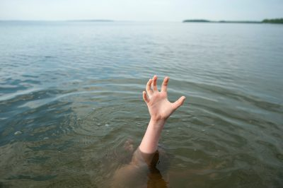 Photo: A hand reaching out of Leech Lake, Walker, MN.