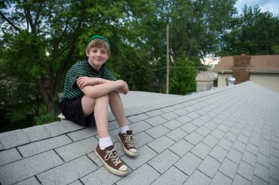 Photo: A young boy perched on a roof, Lincoln, Nebraska.