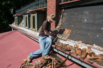 Photo: A teenage boy works on repairing a roof of an old house, Lincoln, Nebraska.