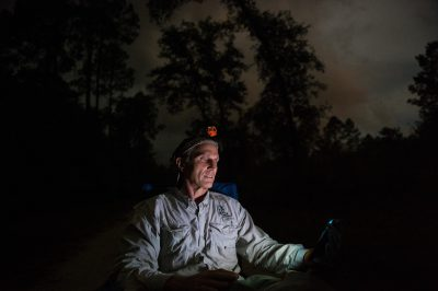 Photo: A man is bathed in the glow of his phone while on a bat bioblitz in the Big Bend Wildlife Management Area near Perry, Florida.