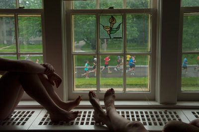 Photo: Two people watch a marathon from the comfort of theirhome.
