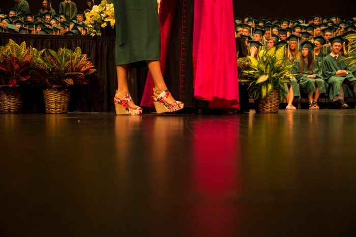 Photo: The feet of teenage girl wearing high heels as she receives her high school diploma.