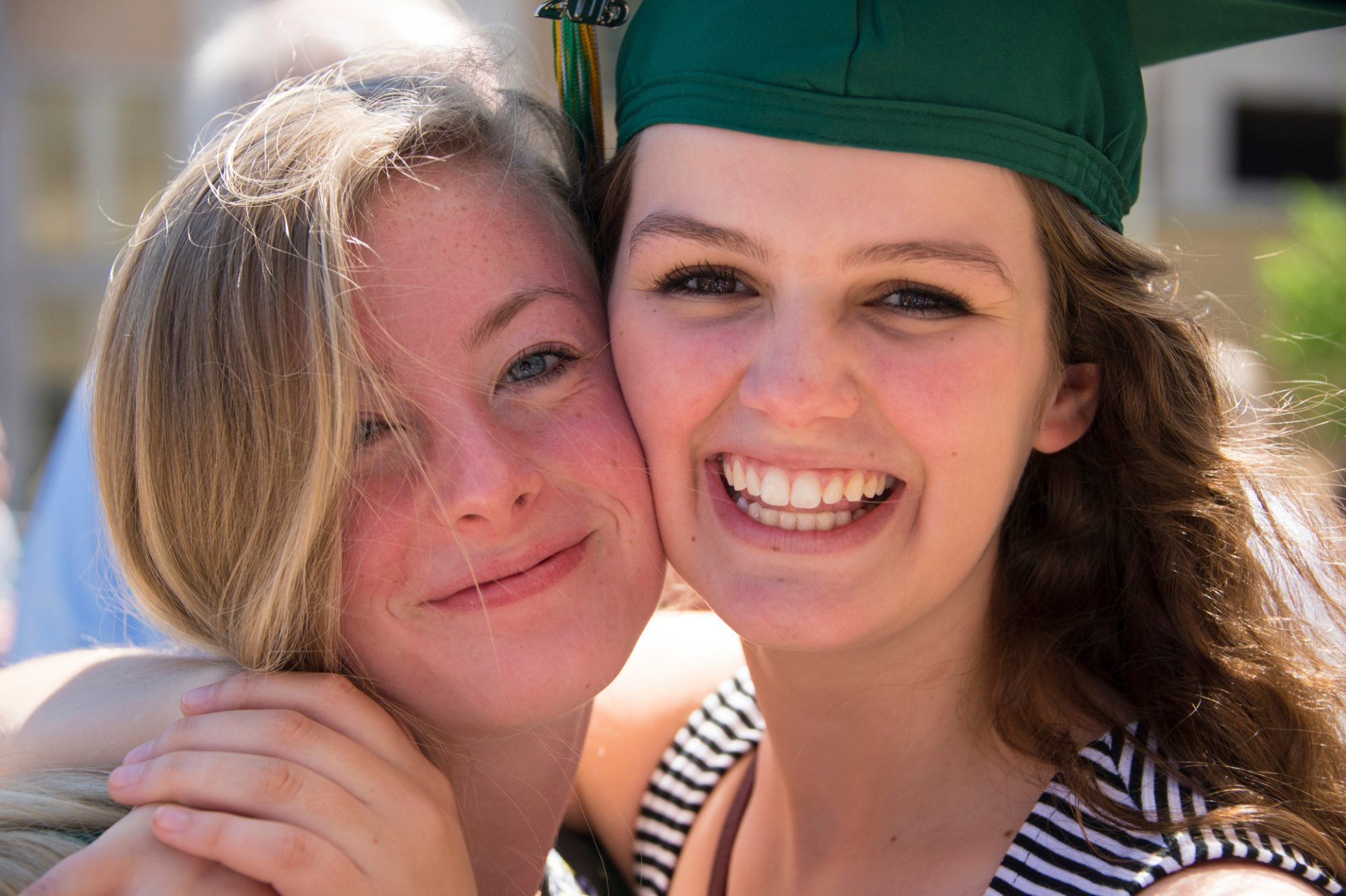 Photo: Two teenage girls hug after their high school graduation ceremony.