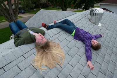 Photo: A teenage girl and her elementary age brother lay on the roof of their grandparent's house.