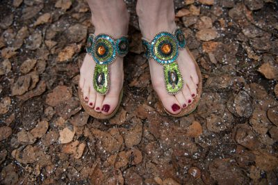 Photo: A woman's feet in sparkly sandals, standing on leaves and graupel.