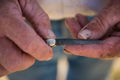 Photo: A detail shot of a man holding a pocket knife in his hands.