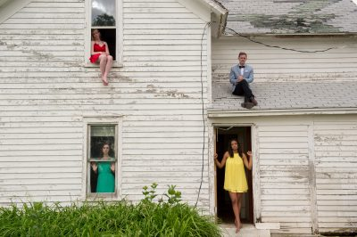 Photo: Teenage girls look out window and doorways while a young man sits on the roof of an old house.