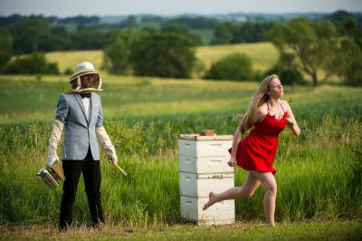 Photo: A man poses with a beehive while a young woman runs past in Bennet, Nebraska.