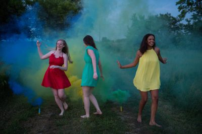Photo: Three young women run through smoke bomb fire crackers in Bennet, Nebraska.