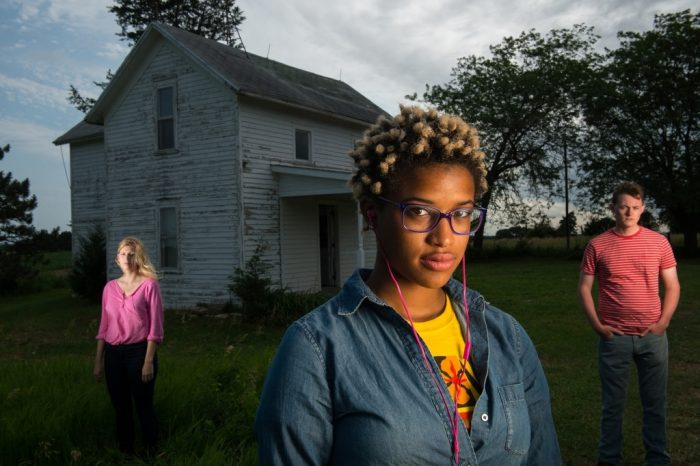 Photo: Three young adults stand outside of an old farmhouse.