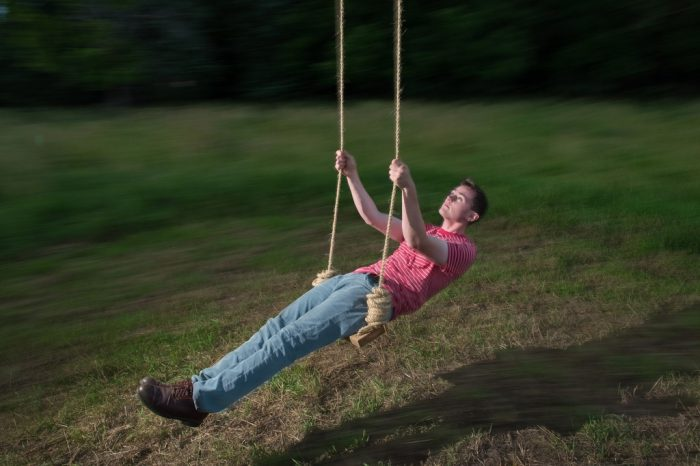 Photo: A young man is shown during a slow shutter on a rope swing.