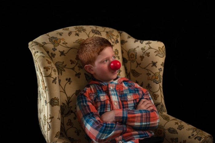 Photo: A young boy with a clown's nose.