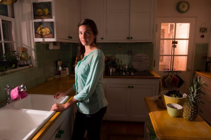 Photo: A young woman poses in her kitchen.