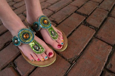 Photo: A young woman with colorful toes and sandals.