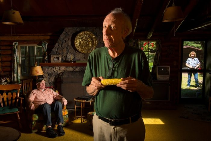 Photo: A man poses with an ear of corn in a log cabin as another man and a woman watch.