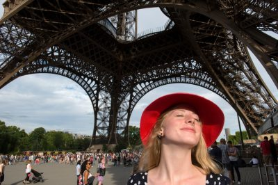 Photo: A teenage girl with a red hat stands under the Eiffel Tower in Paris, France.