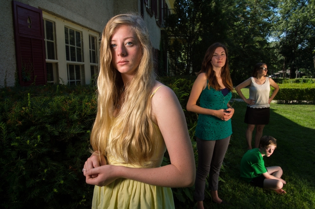 Photo: A group of young women and a young boy are softly lit by soft boxes outside of a house.