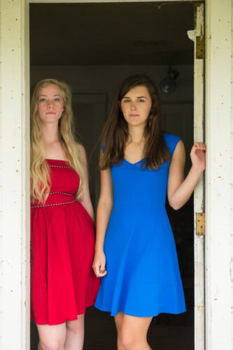 Photo: Two teenage girls in the doorway of an old farmhouse.