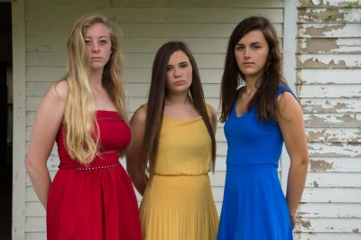 Photo: Three teenage girls on the porch of an old farmhouse.