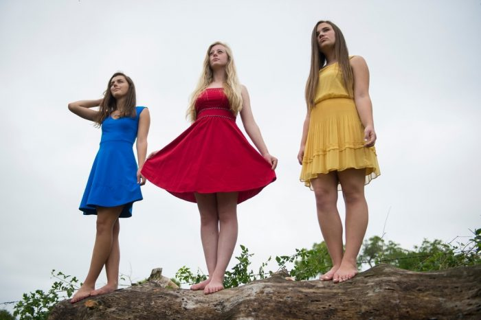 Photo: Three teenage girls stand on a log.