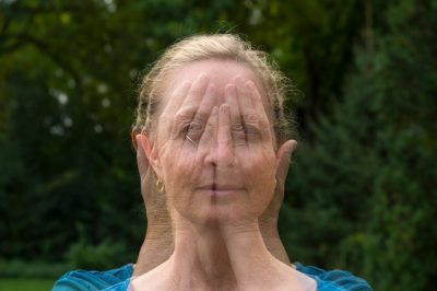Photo: A woman covers her eyes during a double exposure.