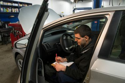 Photo: A mechanic runs a diagnostics test on a car.