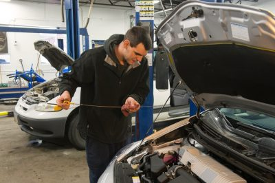 Photo: A mechanic checks the oil level in a car.