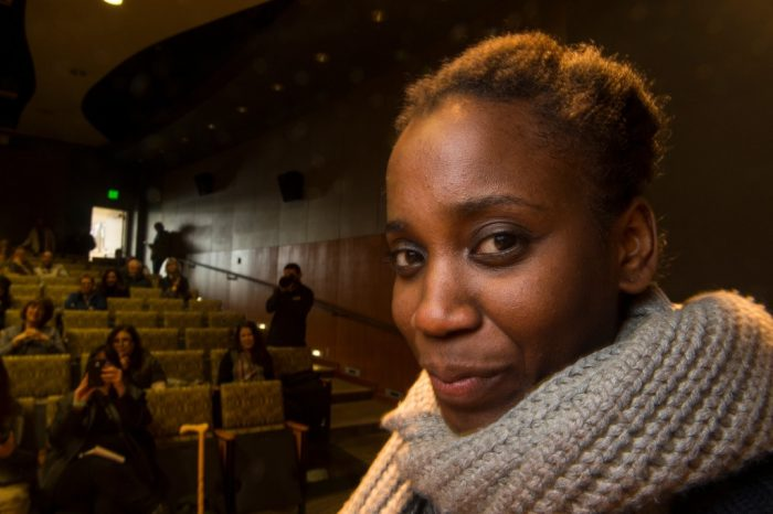 Photo: A young woman is lit softly in an auditorium.