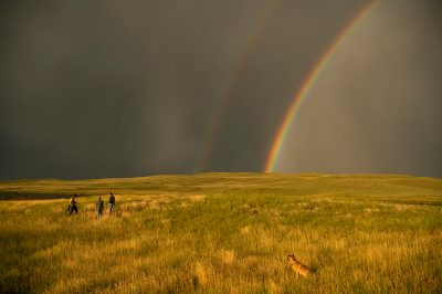Photo: Three people stand in a prairie with a double rainbow in the background.