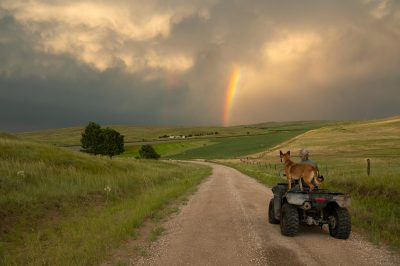 Photo: A woman and her dog drive on a dirt road toward a rainbow.