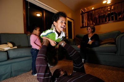 Photo: A father plays with his children after dinner in their home in Lincoln, Nebraska.