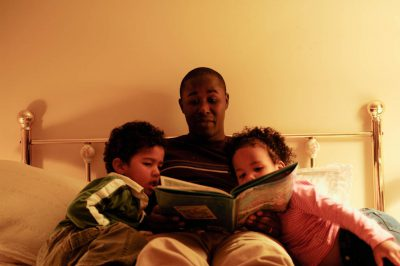 Photo: A father reads his children a bedtime story.