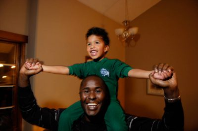 Photo: A boy rides on his father's shoulders in their home in Lincoln, Nebraska.