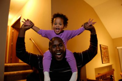Photo: A young girl rides on her father's shoulders in their home in Lincoln, Nebraska.