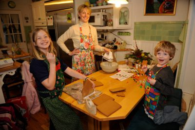 Photo: A mother and her two children make a gingerbread house.