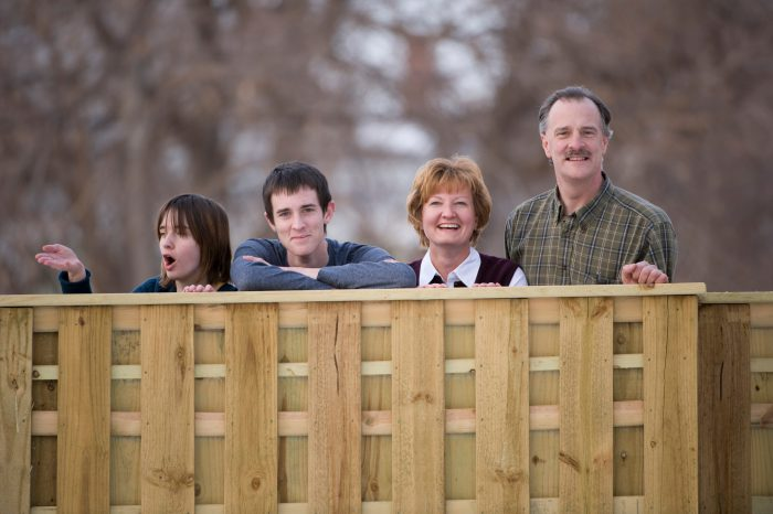 Photo: A family poses for a photo behind their fence.