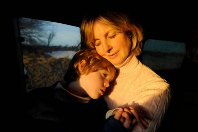 Photo: A mother holds her son while traveling in an old truck.