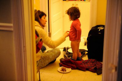Photo: A mother dresses her young daughter in the morning.